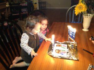 My girls enjoying the light of the Hanukkah candles with their homemade menorah.